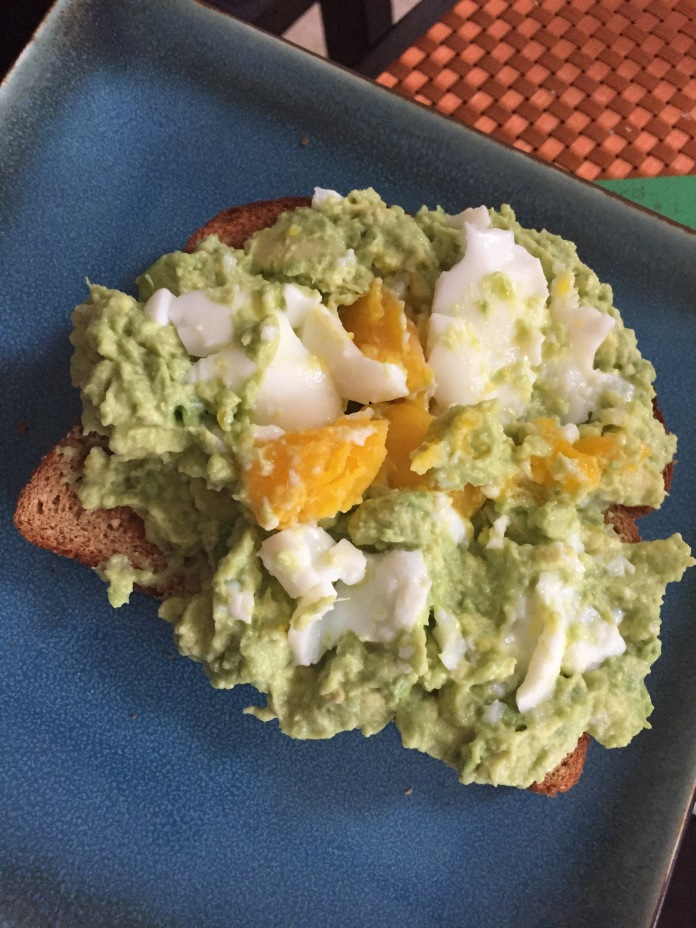 Avocado toast with a mangled boiled egg.